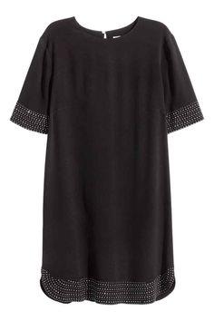Jurk met studs: Een korte, rechte jurk van geweven kwaliteit met een licht onregelmatige structuur. De jurk heeft korte mouwen, studs aan de onderkant en onder aan de mouwen en een splitje met een knoop in de nek. Ongevoerd.