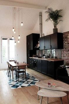 Monochrome kitchen. Exposed brickwork behind the mat black kitchen units. The black and white pattern tiles on the floor add interest.