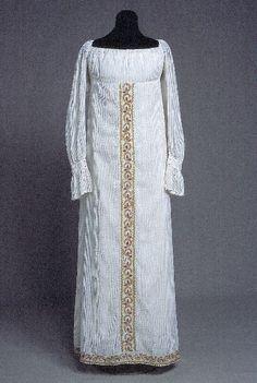 Regency gown KM 9213  Vitt knuttyg med bård på kjolen, mitt fram samt nedomkring. Broderad med kulörta garner. Kort liv med djup halsringning, ärmen går fram till halsringningen på axeln och är rynkad upptill och vid handleden. Linning som knäpps med 2 knappar och knapphål. En volang är rynkad vid linningen, kantad med en liten tränsad udd. Kjolen består av ett framstycke och ett bakstycke, sömmar i sidorna. Knytes samman i ryggen med rynksnoddarna. Ett brett broderat bält