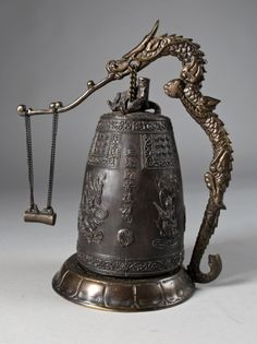 A Chinese bronze bell on stand with Gong.  The bell is finely molded with dragons and nymphs with one line inscription with original dragon shape stand and gong. Height: 11.5, circa 20th century.