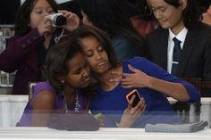 Sasha (L) and Malia Obama, daughters of US President Barack Obama, take a photo of themselves during the Presidential Inaugural Parade on January 2013 in Washington, DC. Malia Obama, Barack Obama Family, Michelle Obama, Obama Daughter, First Daughter, First Black President, Our President, Obama Sisters, Les Innocents