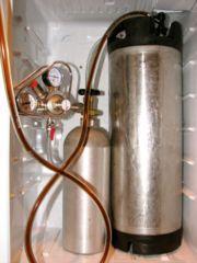 Soda keg for homebrewed beer and 5 pound CO2 cylinder with regulator in kegerator