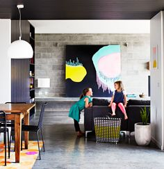 The Black House: Polished concrete floors and besser block walls make for strong features, while vibrant colour pops against a grey backdrop.   A daring black ceiling grounds the space. The striking canvas artwork is by Clare O'donoghue.
