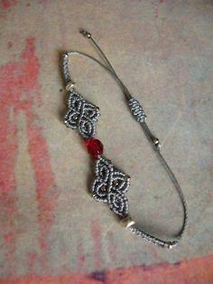 Ein geknüpftes **Armband** in Silbergrau mit eingearbeiteten Silberperlchen und einer leuchtend roten Glasschliffperle. Material: S-Lon Cord (Nylon) Es ist mit Schiebeverschluss...