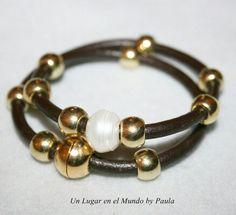 Pulsera de cuero con piezas metalicas doradas y perla natural.