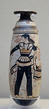 Amazon wearing trousers and carrying a shield with an attached patterned cloth and a quiver. Ancient Greek Attic white-ground alabastron, c. 470 BC, British Museum, London