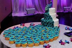 Peacock themed wedding cake with tail of cupcakes
