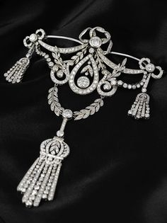 A vintage platinum and diamond corsage / pendant, 1920s. In the Belle Epoque taste, the brooch with garland, ribbon and tassel motifs, suspending a tassel and set throughout with brilliant-cut diamonds, mounted in platinum. #vintage #brooch #pendant