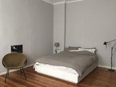 Schlichte Schlafzimmer-Einrichtung mit grauer Wandfarbe sowie grauem Bettbezug. Wohnung in Berlin.  #Berlin #apartment
