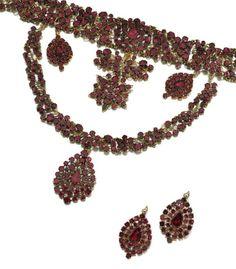 Gilt metal and garnet demi-parure, second half of the 18th century   A necklace en esclavage, two detachable drops, an additional pair of detachable drops, girandole ear pendants and an aigrette