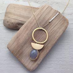 Collier long en laiton doré monté d'une demi-lune en laiton doré mat et d'une pierre semi-précieuse grise (+- 18mm) sertie plaqué or. La chaine est également ornée de petites perles fines d'un côté.