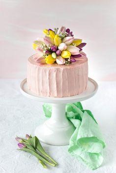 Diese leckere Erdbeer-Holunder-Torte wird durch ein Blumenbouquet aus Tulpen und Schleierkraut geschmückt, die nach dem Anschneiden als Tischdeko dient.