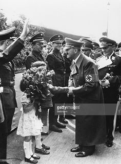 Rose handed out -- not tossed -- to Hitler. Berlin, Germany: Adolf Hitler, whose face was painfully scratched when a bouquet of roses was tossed into his car when he entered the Sudentenland, receives a bouquet of roses from two little children from the Sudentenland as he arrives at the Anhalter railway station in Berlin after his triumph at the four power conference in Munich. Behind Hitler is Field Marshal Hermann Goering (holding baton) and Propaganda minister Goebbels. Members of the…