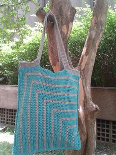 Bolsa de crochê feita de barbante nas cores turquesa e cinza. Tem forro cinza e fechamento interno com cordões de crochê.