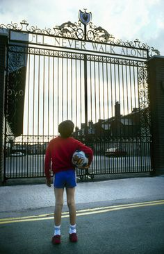 A young footballer looks up at the Shankly Gates at Anfield and dreams of pulling on the red shirt for his club during the 1980s