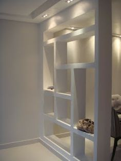 Separador de ambiente de gesso com iluminação embutida - um coringa na decoração de interiores. Permite exposição de objetos além de dividir ambientes mantendo a claridade.