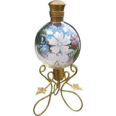 This is a very unique and decorative vintage perfume bottle on an ormolu stand in excellent condition. The clear glass is in the shape of a ball by marisa
