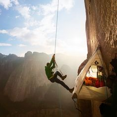 Tommy Caldwell uses a network of ropes to move between sections of the Dawn Wall, a granite expanse of Yosemite National Park's El Capitan. After living on the wall for 19 days, Caldwell and Kevin Jorgeson reached the summit today, becoming the first to ever free climb the entire Dawn Wall. Photograph by Corey Rich, Big Up Productions.