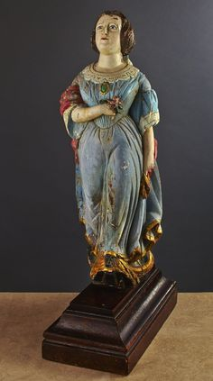 "Mid 19th century English ship's figurehead. Fine classical full figure in stepping position of a young women in a period gown with a brooch at the neckline. She holds a rose in her right hand. A shawl in her left hand is draped across her back over the lacing board to her right arm. The original mounting (""drift"") pin is intact and protrudes at the back of the lacing board. Polychrome English figurehead circa 1850 - 1860 on a custom made pedestal. Height on stand 52 in. Condition is very…"
