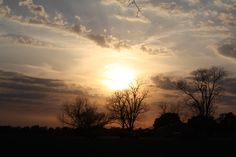 the clouds look like angel wigs on each side of the sun, I took this at the dead end of moms road , the sunset in the field