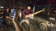 A man breaks the window of a police van with a wooden plank during a protest in Yuyao. October 2013