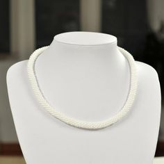 Unique handmade shiny white bead necklace made of white beads and thread.