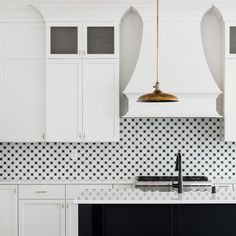 Vintage brass lanterns light a black center island contrasted with a white quartz countertop and complemented with an oil rubbed bronze faucet mounted above a farmhouse sink.