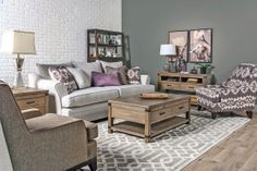 Pops of purple on the Palmyra Collection's woven fabric sofa and ikat accent chair bring fashionable flair that's enhanced by mirrored and metallic accessories, while the Rhodes Collection's wood occasional tables and Livingston Drop front Desk provide rustic relief.