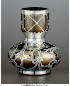 AN AUSTRIAN GLASS BUD VASE WITH SILVER OVERLAY Glass attributed to Glasfabrik Johann Loetz Witwe, Klostermuehle, Austria; silver maker unidentified, circa 1900 Marks: glass marked 57; silver marked (fish), STERLING 4-1/8 inches high (10.5 cm). #SterlingSilverMarks