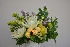 Stunning white king protea feature in this generous arrangement. Oak foliage, pincushions, leucs & roses in a marbled pot.