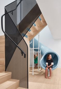 Walker's centrepiece is the children's spiralling blue slide, which plummets through the heart of the house and connects the basement level to the ground floor. Interior Stairs, Apartment Interior, Wooden Staircases, Stairways, Walker House, Wood Cladding, Stair Railing, Railings, House Entrance