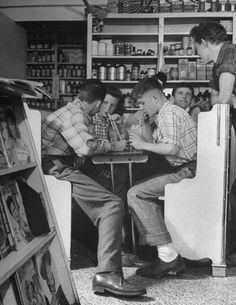 Des Moines, Iowa, 1945. Teenage boys and girls drinking milkshakes in drug store.