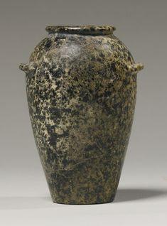 AN EGYPTIANHARDSTONE WAVY-HANDLED JAR, PREDYNASTIC PERIOD, NAQADA III, CIRCA 3200-3000 B.C.