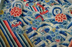 In vibrant blues, greens, reds, and yellows, intricately embroidered motifs rich with symbolism cover this Chinese silk jifu from around 1900.