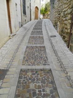 Combination of long, shallow steps for people and sloping setts for vehicles with surface water channels incorporated. Beautifully detailed and constructed. Uzes, France.