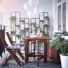 Ein Balkon mit ÄPPLARÖ Klapptisch, Klappstühlen und Banktruhe in Braun, auf den Stühlen HÅLLÖ Kissen in Beige und RUNNEN Bodenrosten in Braun auf dem Fußboden