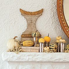 Traditional Pumpkin Mantel | Choose an assortment of small pumpkins and squash in muted colors that complement the surrounding style. Bring in other items from around your home that you wouldn't normally think to pair with pumpkins, such as julep cups and old books covered in elegant paper. The key is to keep the look simple by sticking to the same basic color tones.