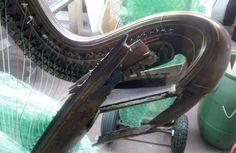 An Erard gothic harp whose soundbox has splintered. The damage is probably a result of using modern pedal harp strings on an antique harp, which was built for lighter-tension strings. The difference in tension is substantial, and the more lightly built harp cannot withstand it.