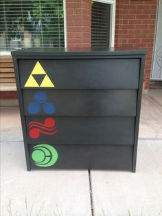 Legend of Zelda themed chest of drawers painted with Annie Sloan Graphite, English Yellow, Napoleonic Blue, Emperor's Silk, and Antibes.   https://www.facebook.com/JensFurnitureRehab