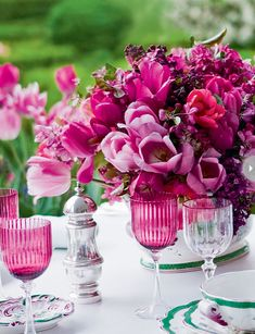 Matching Magic....A shock of fuchsia serves as centrepiece for this alfresco tablescape, as tulips in a spectrum of pink are buoyed by cuttings from Carolyne's crabapples and lilacs. To create continuity, she matched every element, taking notes from the garden setting for the flowers on the table (all in bloom at the time) and the tableware (cranberry stemware and china with a pink flower motif).