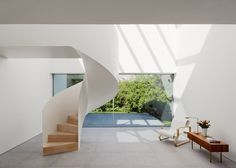 A spiral staircase provides an eye-catching feature inside this minimal white house