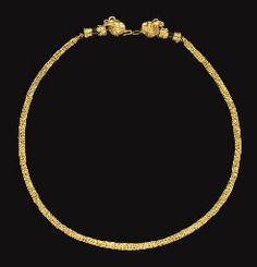 A GREEK GOLD AND BLACK STONE NECKLACE  HELLENISTIC PERIOD, CIRCA 3RD-2ND CENTURY B.C.  Formed of a length of three-fold double loop-in-loop chain, each end threaded through a capped cylindrical black stone bead, one end with a plain sheet cap edged with ropes, one end with filigree spirals edged with ropes, the terminals in the form of horned lion heads, petal-like ears on either side of the stylized looped horns, the back of the heads embellished with beaded filigree,  15½ in. (39.4 cm.)…
