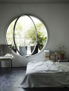 "A large horizontal-swing, pivoting oeil-de-boeuf, (""ox's eye"") window provides a dramatic counterpoint to the simplicity of this bedroom."