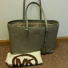 Michael kors laptop work bag Light  Grey leather laptop bag extremely roomy,  had many pockets middle pocket is padded for a laptop.  Recieved many compliments with this bag. Used it for for less than a few months.  Comes with a duster bag.  No stains or mark on the bag.  The bag looks crinkled on the side but it's not worn out. Michael Kors Bags