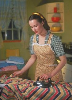 retro housewife ironing in her apron.......and she looks so happy doing it too!!!!  I, on the other hand, do NOT look, nor feel happy when I'm ironing anything.....not even my aprons!!