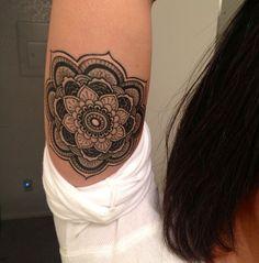 Cute little black-ink mandala flower tattoo for girls on upper arm