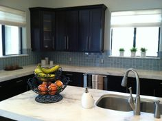 Great before and after pictures. Arctic blue glass subway tile...12.99 a sf on ebay. Black cabinets.