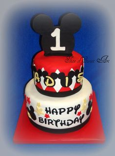 Torta de 2 pisos circulares en doble altura con cubierta en fondant blanco y rojo y decoraciones en los mismos tonos, con mensajes en letras walter para celebrar 1 año