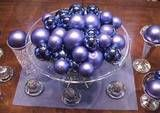 Christmas Centerpiece of Ornaments in a Pedestal Bowl:   Arrange colorful ornaments in a footed bowl.   FromCoral Nafie. A simple pedestal bowl holds colorful Christmas ornaments. Centerpiece Idea:   If you have a simple footed bowl in your home, you can create this dramatic centerpiece for your Christmas (or any other special occasion) table. We've chosen beautiful lavendar and purple balls in matte and shiny finish to coordinate with the decor of the home. Even though these are not…