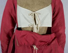 1800-10. This dress is styled with a drop-front bodice, known as bib front or apron front. The bib attaches to the dress with pins on the sides—you can see marks on the fabric where the bib was originally pinned. Under the bib front is an ivory cotton underbodice that closes with ties. The dress, held for years in a private collection, is completely hand sewn.